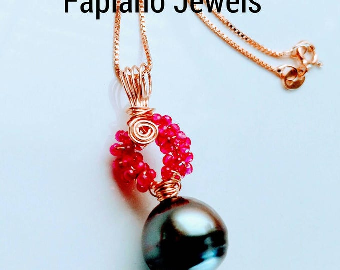 Black Tahitian pearl pendant, ruby pendant. Silvery black natural pearl hangs from a circle of rubies. Pearl necklace on a gold chain