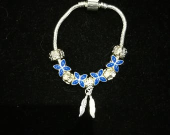 Blue European bracelet with charms at night, feathers