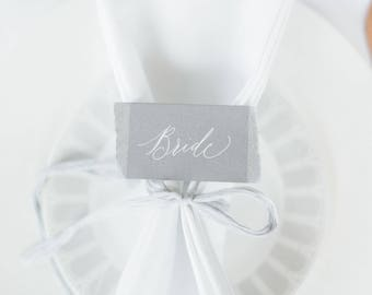 Light grey torn edge calligraphy wedding place names