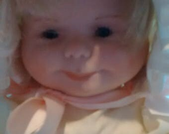Unusual doll with three different faces. One sleeping, one crying, and one smiling