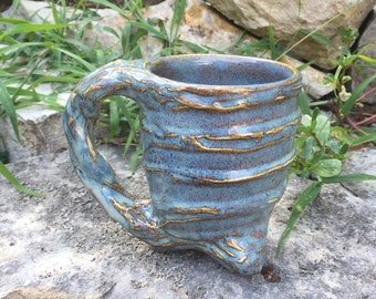glossy blue and beige tripod mug with textured exterior