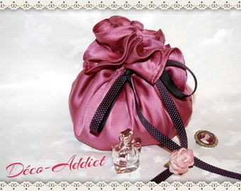 Old pink satin pouch and a black ribbon with polka dots pink