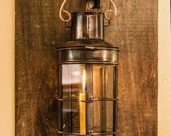 Candle lantern mounted on recycled wood