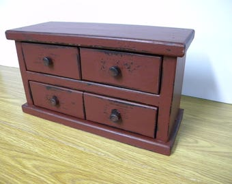 Four drawer apothecary table or counter cabinet. Distressed cranberry red.