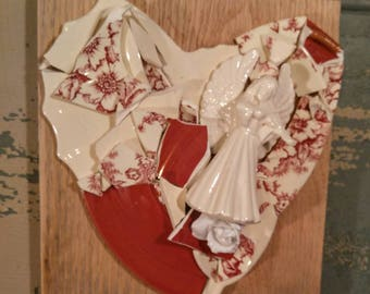 Broken and beautiful mixed media, wall mounted heart collage with broken ceramics in ivory, dark red and red floral and a ceramic angel.