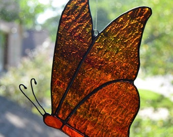 Stained glass butterfly suncatcher with orange and red wings and body 5 x 7