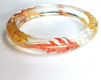 Bracelet fin avec inclusion de feuilles rouges, jaunes et oranges