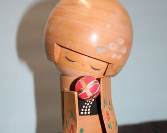 Kokeshi doll; 1970's Japanese Kokeshi girl with toy; chop mark, foil label; Schmid Bros copyright
