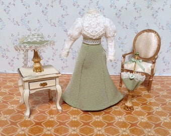 A dressed mannequin in a Victorian ivory blouse and green skirt.