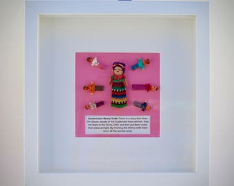 Guatemalan worry doll picture  in white box frame with 3 separate worry dolls in pouch.