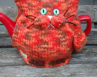 Hand-knitted Marmaduke the ginger cat tea cosy.