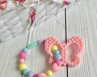 Rainbow colored carrier chew with a butterfly teether