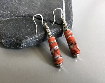 Long drop earrings in coral color decorated with silver.