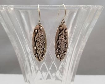 Handcrafted textured sterling silver dangle earrings with southwestern style feather applique