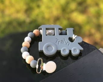Gray pacifier clip and train toy set