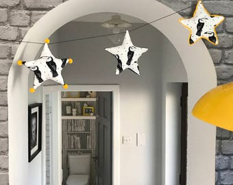 Monochrome toucan garland with yellow accent.
