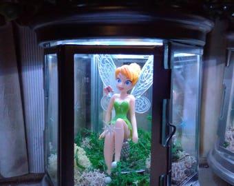 fairy sitting on a thimble garden lantern