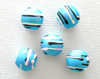 5 light blue glass beads with black and white lines
