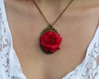 Red Rose bloom on a bronze medallion