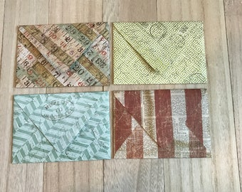 Four lined envelopes with notecards. Newsprint design