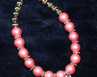 Pink beaded bracelet with butterfly charm