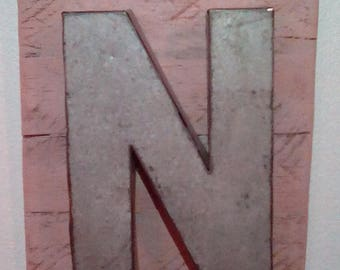 Initial N wall hanging decor on distressed pallet wood. Beige milk paint wash with as bit a rose. Galvanized steel capital N.