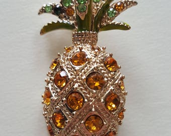 A Monet pineapple brooch 2 in x 3/4 in with orange,green,and black cubic zirconia