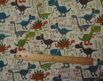 White with Multicolored Dinosaurs and Words Flannel Fabric By the Yard