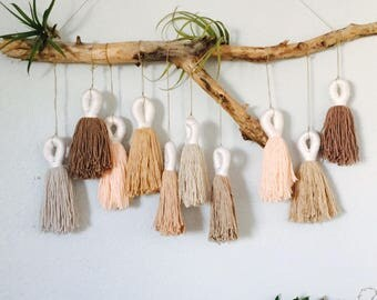 Neutral colored tassel wallhanging on driftwood