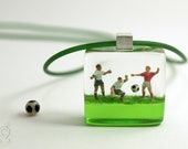 Soccer thriller – Playful resin pendant with three soccer players and a ball on green grass for all world champions