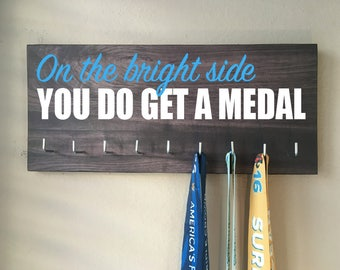 "Race Medal Holder - ""On the bright side you do get a medal"" white and blue with dark gray wood grain background"