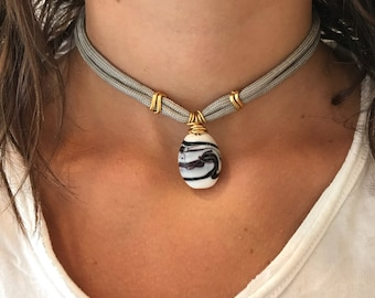Cermaic choker on grey cord.