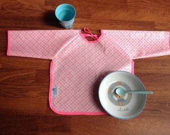 Bavoir à manches en coton enduit Petit Pan aux motifs Momoyo rose fluo