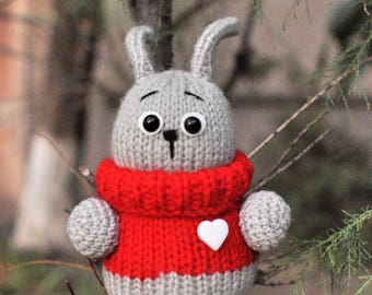 Small fat knitting Bunny. Knitting crochet toy. Hare. Gray Rebbit in red sweater.