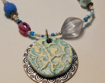 This lacy ceramic  necklace looks like the pastel sky on an early summers morn