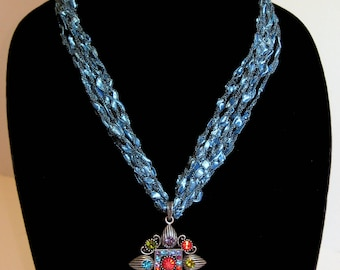 Crocheted necklace in blue with multi colored pendant