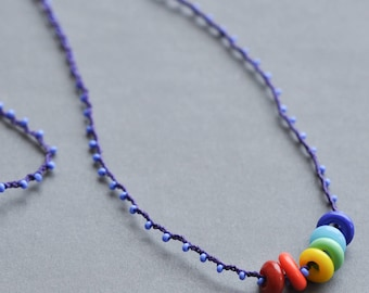 Rainbow rings on chrocheted purple, itty bitty, over-the-head strand