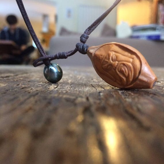 One of a kind necklace made of a tahitian pearl and an amazing carved pumpkin seed. Man necklace tahitian pearl.