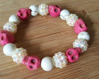 Pink and white stretch bracelet with skulls