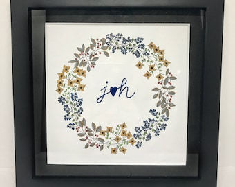 Hand drawn wreath with initials linked by heart.