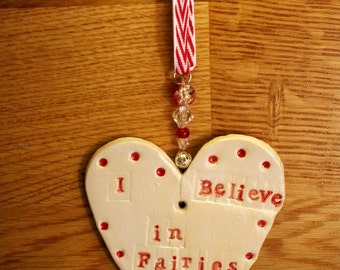 I Believe in Fairies Pottery Heart with white and red glazes. Handmade and sent to you in a lovely gossamer bag ready to be given as a gift.