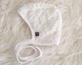 Neutral white cream ruffle fabric pilot hat by Little Lapsi. Baby hat with ties. modern