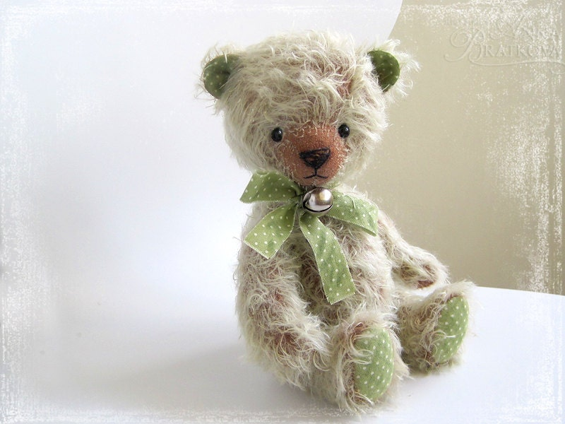 green and grey stuffed animal teddy bear with bow and bell