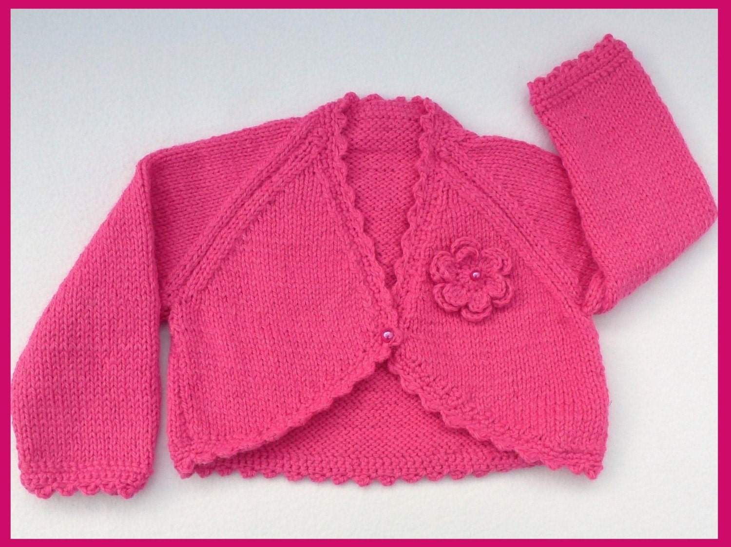 Baby sweater. Baby girl hand knitted raspberry pink bolero cardigan to fit 3 to 6 months