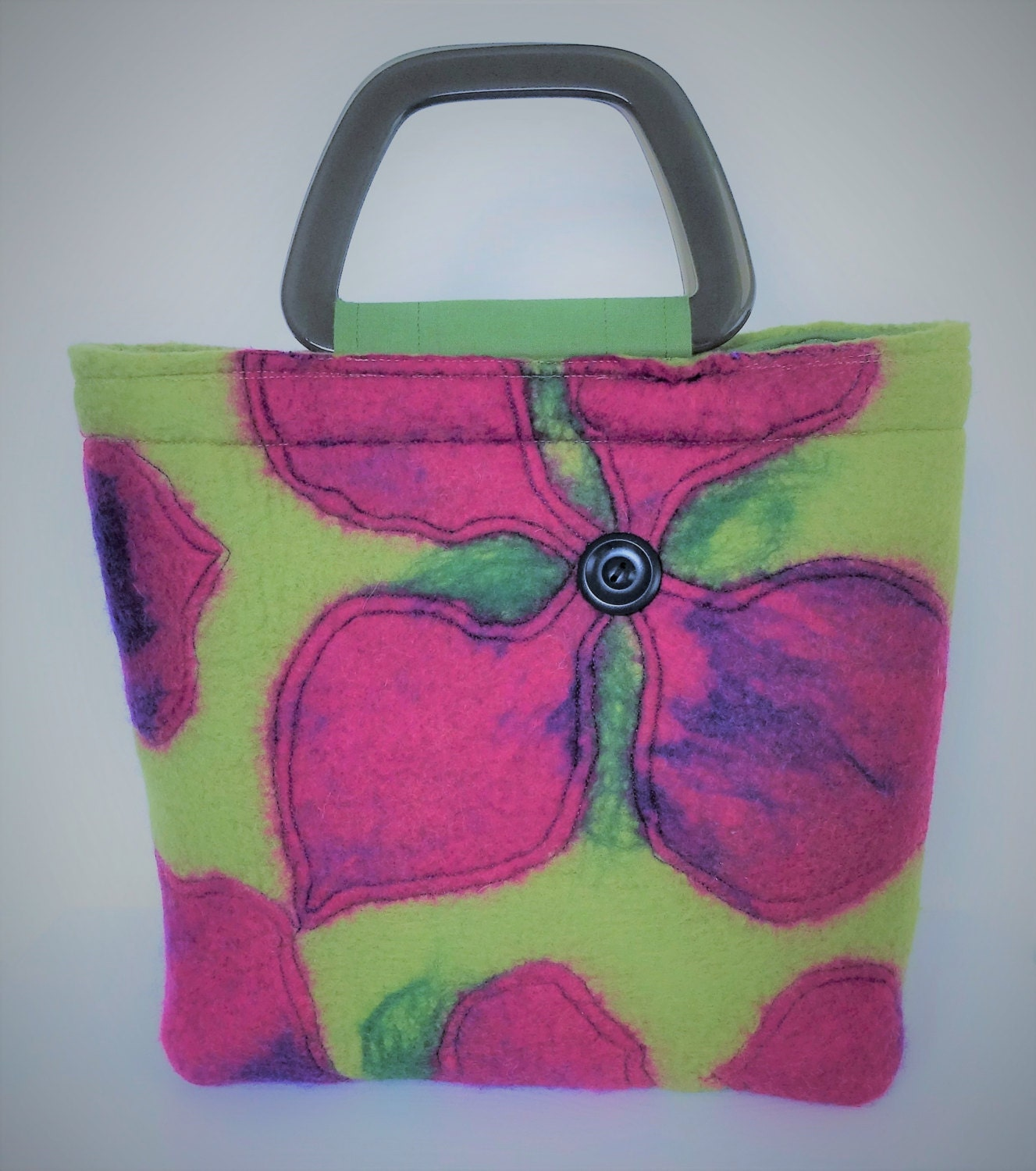 Handfelted handbag in cerise and olive green with stylised Frangipani flowers as decoration. Mediumlarge in size and designer made.