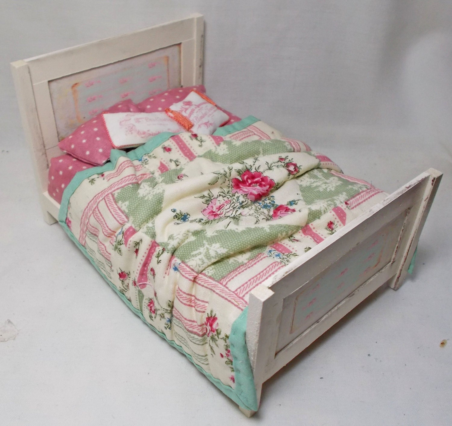 Dolls House Antique Cream Wooden Unmade Bed with Pink  Green quilt.