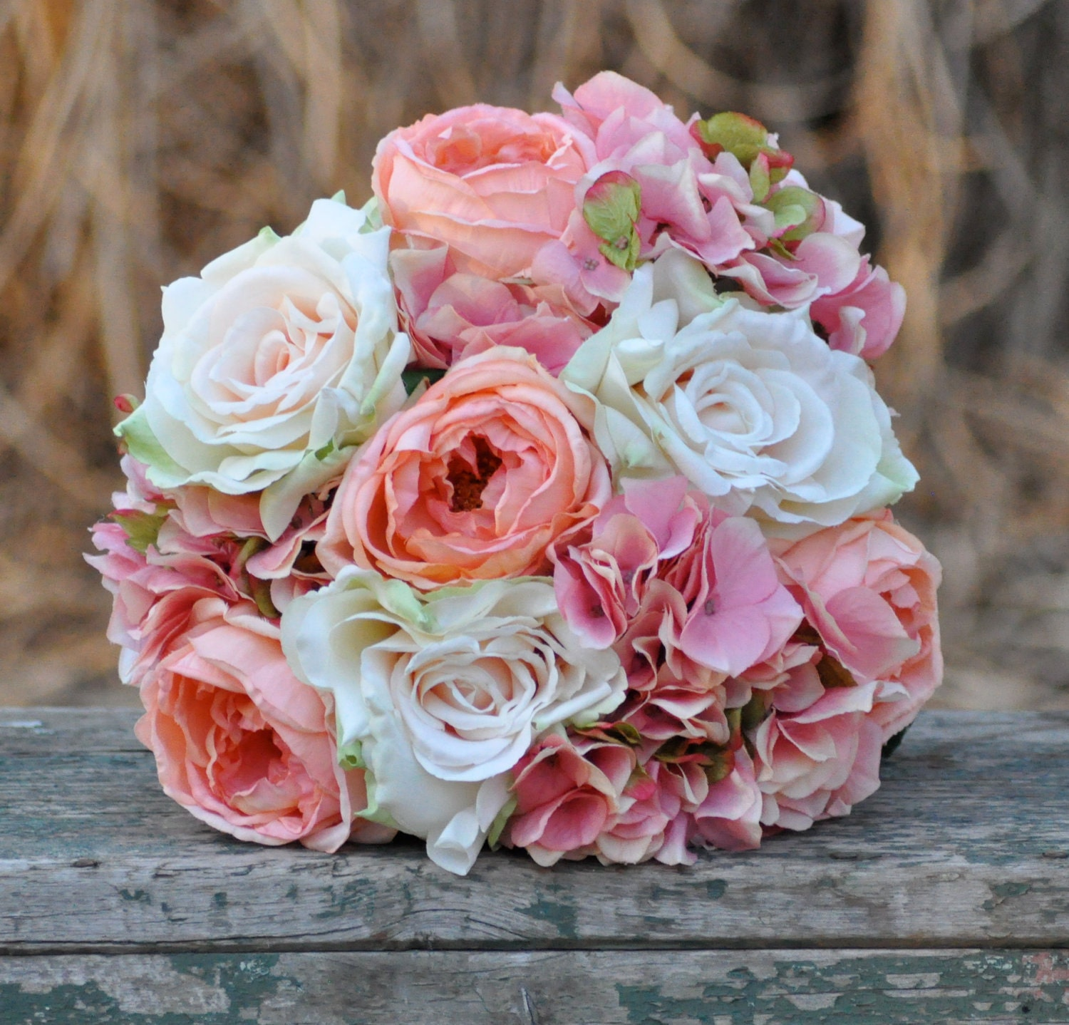 Coral rose, blush rose and pink hydrangea wedding bouquet made of silk roses.
