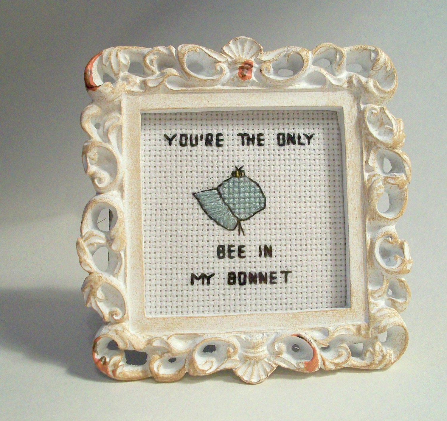 """You're the only bee in my bonnet -- TMBG """"birdhouse in your soul"""" lyric in small cross stitch"""