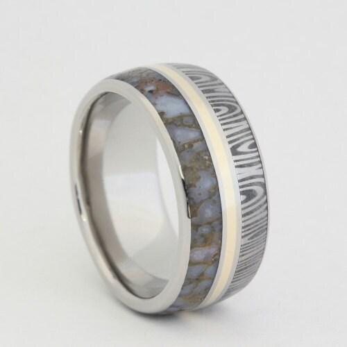 titanium ring inlaid with damascus dinosaur bone by