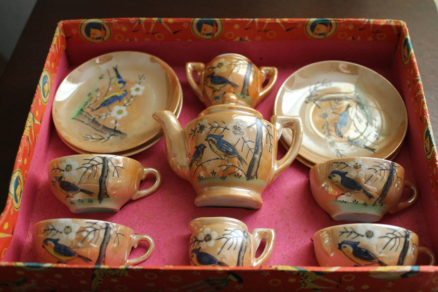 a vintage children's tea set with artistic detailing of birds